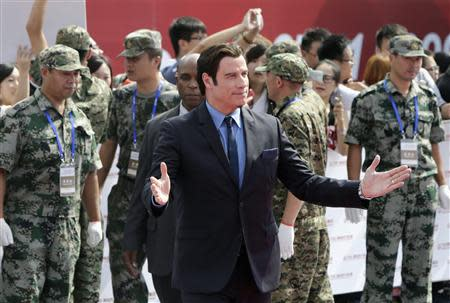Actor John Travolta of the U.S. gestures to fans as he arrives for the launch ceremony of the Qingdao Oriental Movie Metropolis on the outskirts of Qingdao