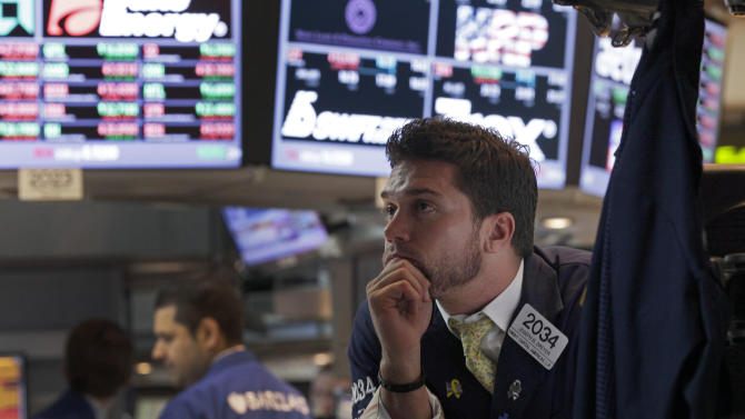 Specialist Joseph Dreyer, right, watches the decision of the Federal Reserve as he works at his post on the floor of the New York Stock Exchange Wednesday, June 20, 2012. The Federal Reserve is extending a program designed to drive down long-term interest rates to spur borrowing and spending. (AP Photo/Richard Drew)