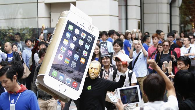 A man wearing a mask depicting Steve Jobs holds up a cardboard cut-out of Apple's new iPhone 6, as he walks into the Apple Store in Tokyo