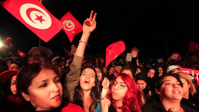 Supporters of the Nidaa Tounes secular party movement wave flags and shout slogans in Tunis