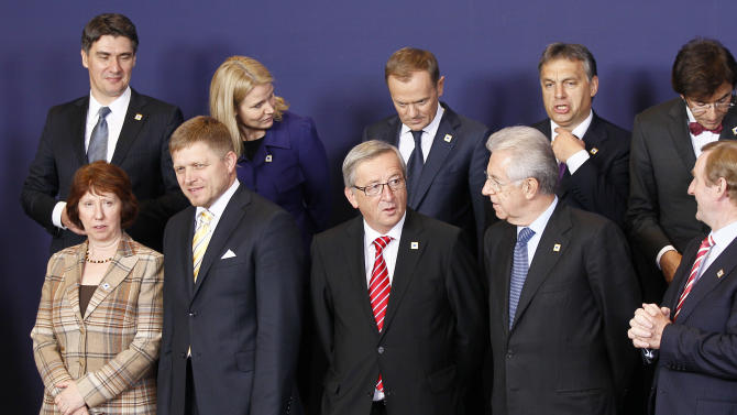 Front row left to right, EU High Representative Catherine Ashton, Slovakian Prime Minister Robert Fico, Luxembourg's Prime Minister Jean-Claude Juncker, Italian Prime Minister Mario Monti and Irish Prime Minister Enda Kenny. Back row left to right, Croatian Prime Minister Zoran Milanovic, Denmark's Prime Minister Helle Thorning-Schmidt, Poland's Prime Minister Donald Tusk, Hungary's Prime Minister Viktor Orban and Belgium's Prime Minister Elio Di Rupo pose during a group photo opportunity at an EU summit in Brussels on Thursday, Oct. 18, 2012. European leaders are gathering again in Brussels to discuss how to save the euro currency from collapse and support countries facing too much debt and not enough growth. (AP Photo/Remy de la Mauviniere)