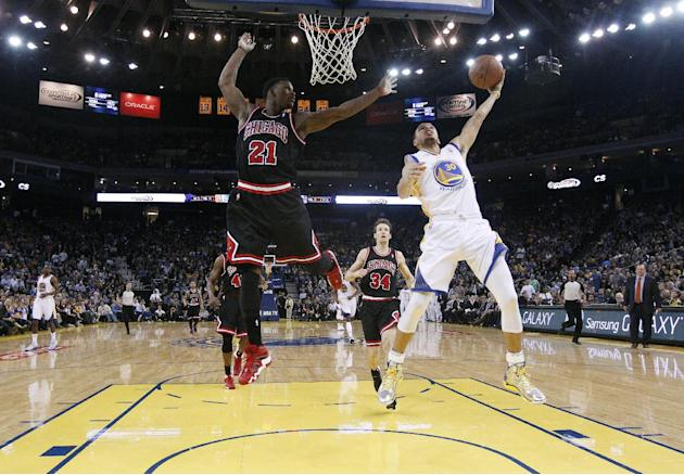 Golden State Warriors' Stephen Curry (30) scores past Chicago Bulls' Jimmy Butler (21) during the second half of an NBA basketball game on Thursday, Feb. 6, 2014, in Oakland, Calif. Golden Sta