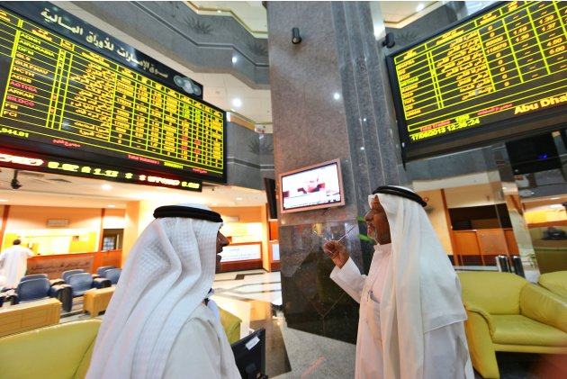 Investors speak as they monitor stocks at the Abu Dhabi Securities Exchange