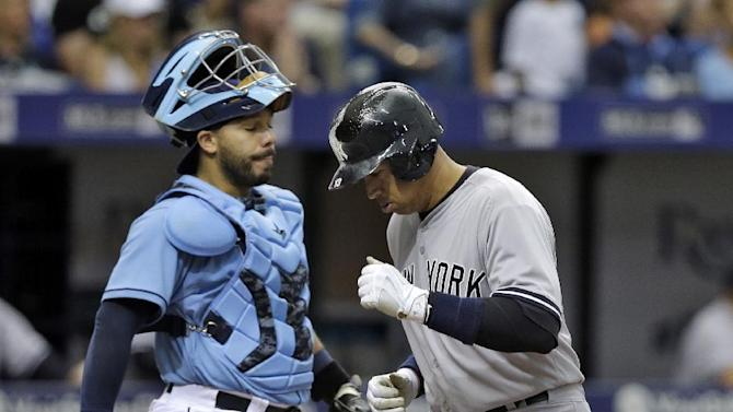 New York Yankees' Alex Rodriguez, right, scores in front of Tampa Bay Rays catcher Rene Rivera on an RBI double by Yankees' Chase Headley of Rays pitcher Steven Geltz during the fifth inning of a baseball game Sunday, April 19, 2015, in St. Petersburg, Fla. (AP Photo/Chris O'Meara)