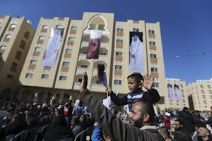 """Posters depicting Qatar's former Emir Sheikh Hamad bin Khalifa al-Thani and Emir of Qatar Tamim bin Hamad al-Thani are seen on a building as Palestinian man holding his son waves during the opening ceremony of """"Hamad City"""", in the southern Gaza Strip"""