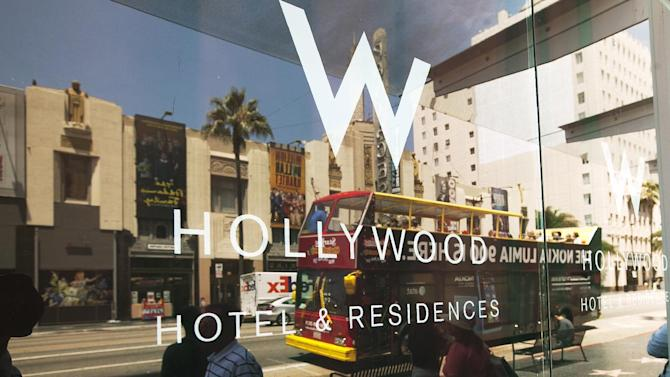 FILE - In this Tuesday, July 17, 2012 file photo, pedestrians pass by the entrance to the W Hollywood hotel and residences in Los Angeles. Starwood Hotels & Resorts Worldwide Inc. says its third-quarter earnings fell more than 7 percent from last year when a one-time gain helped results. The company best known for hotel brands like Sheraton, Westin and St. Regis earned $157 million, or 81 cents per share, in the quarter that ended Sept. 30. That's down from $170 million, or 87 cents per share, last year, when it booked a $23 million gain. (AP Photo/Damian Dovarganes, File)
