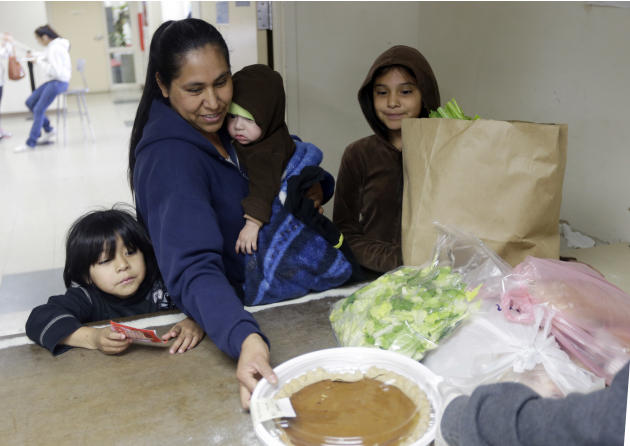 A family receives aid at a food pantry at Sacred Heart Community Service on Friday, Feb. 21, 2014, in San Jose, Calif. Silicon Valley is entering it's fifth year of unfettered growth, with among the h