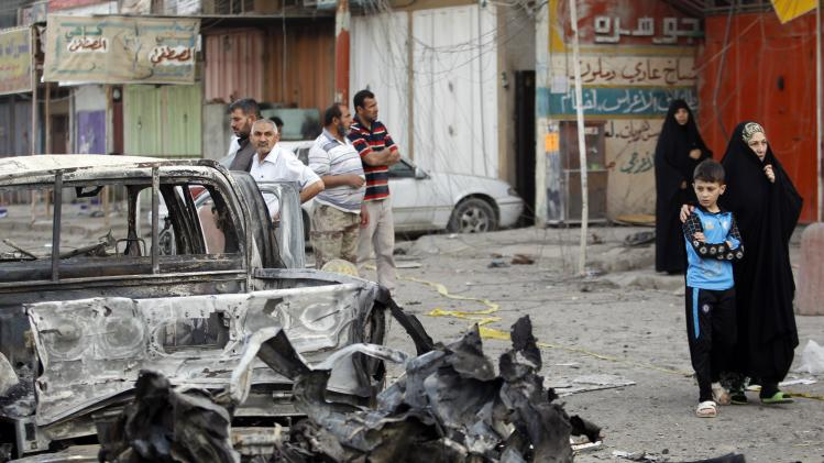 People gather at the site of a bomb attack in Baghdad's Habibiya district