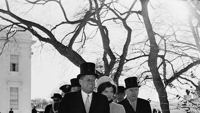 FILE - This Jan. 20, 1961 black-and-white file photo showsPresident John F. Kennedy and Mrs. Kennedy walk outside the White House during inauguration ceremonies, just as the parade began. An 8-inch snowfall on the eve of John F. Kennedy's inauguration in 1961 left hundreds of cars marooned and thousands more abandoned. It will be the first up or down fact check of a Barack Obama campaign pledge for his second term:  Promised warmer Inauguration Day weather.  Will he _ or Mother Nature _ deliver?  It's looking like an uncomfortably close call _ the emphasis on the word uncomfortable for people who will be outside on what's predicted to be a downright chilly day. (AP Photo, File)