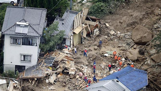 In this aerial photo, rescue workers search for survivors after a massive landslide swept through residential areas in Hiroshima, western Japan, Wednesday, Aug. 20, 2014. A several people died and at least a dozen were missing after rain-sodden hills in the outskirts of Hiroshima gave way early Wednesday in several landslides. (AP Photo/Kyodo News) JAPAN OUT, MANDATORY CREDIT