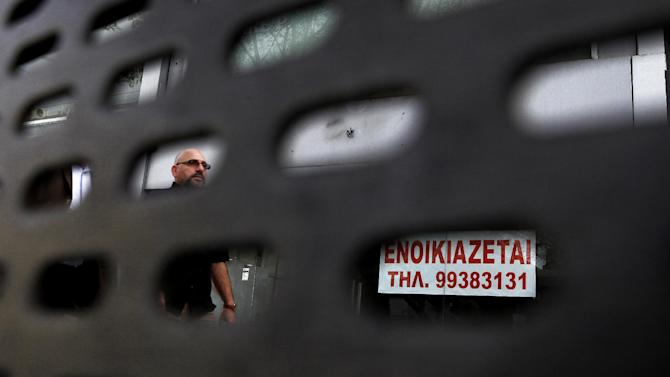 Seen through a bus stop bench, a man passes an empty shop with a sign reading in Greek 'for rent' in central capital Nicosia, Cyprus, on Saturday, March 30, 2013. Big depositors at Cyprus' largest bank may be forced to accept losses of up to 60 percent, far more than initially estimated under the European rescue package to save the country from bankruptcy, officials said Saturday. (AP Photo/Petros Karadjias)