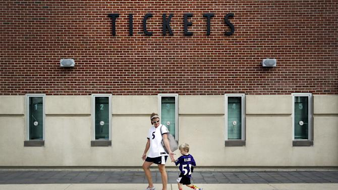 Kristen Moyer receives a high-five from her son Tyler, 4, after they traded in his Baltimore Ravens running back Ray Rice jersey, Friday, Sept. 19, 2014, at M&T Bank Stadium in Baltimore. The Ravens offered fans a chance to trade in their Rice jerseys for those of another player after he was cut by the team and suspended indefinitely by the NFL for domestic violence
