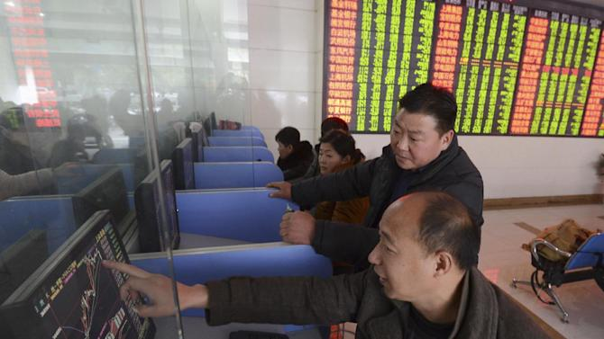 Chinese investors check stock prices on computer terminals at a brokerage house in Fuyang in central China's Anhui province Friday, Nov. 27, 2015. China's stock market fell sharply Friday as investigations into the securities industry widened to include two top brokerages. (Chinatopix via AP) CHINA OUT