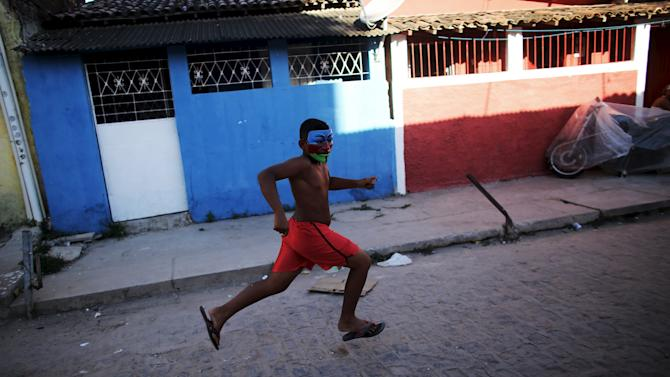 Masked boy runs on a street during one of the many carnival parties to take place in the neighbourhoods of Recife