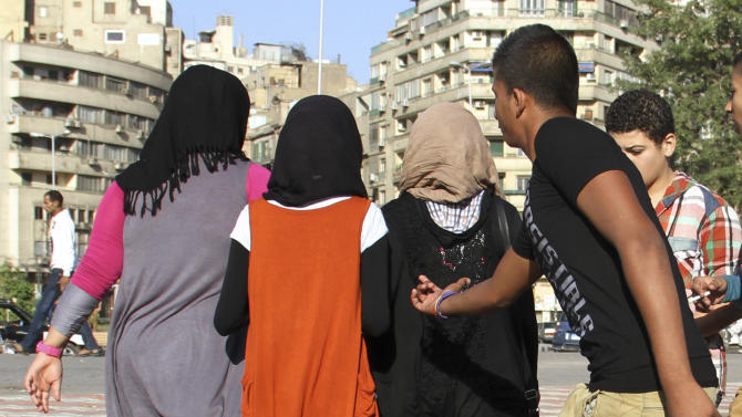 A youth reaches out as young girls walk past near Cairo's Tahrir Square in this Sunday Oct 28 2012 photo. A group of Egyptian men had a mission for this year's Eid al-Adha, Islam's biggest holiday, which began Friday. They wanted to make some effort to stop sexual harassment of women, which in past years has spiked in Cairo during the holiday celebrations with the crowds of rowdy men in the streets. In past years, the Eid has seen major instances of harassment, with crowds of young men groping passing women — so heavily that women had to flee into shops, and for days afterward newspapers decried the mob attacks. (AP Photo/ Mohammed Abu Zeid)