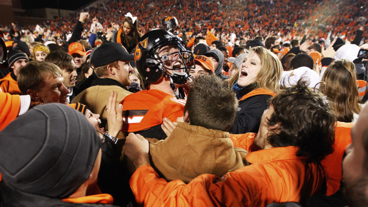 Oklahoma State quarterback Brandon Weeden, center, celebrates with fans following a 44-10 victory over Oklahoma in an NCAA college football game in Stillwater, Okla., Saturday, Dec. 3, 2011. (AP Photo/Sue Ogrocki)