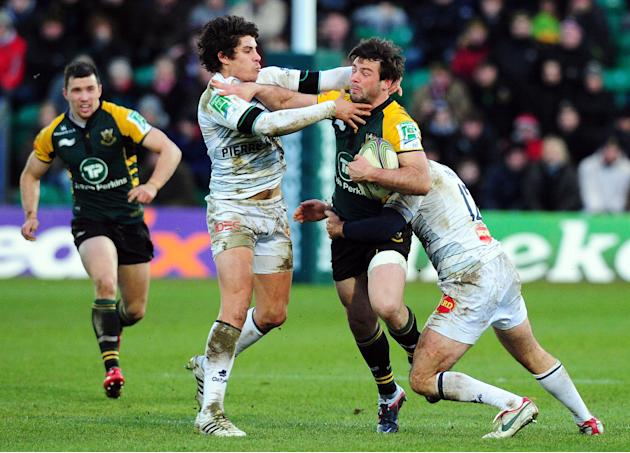 Pierre Bernard of Castres Olympique (2R) tackles Ben Foden (R) of the Northampton Saints during the Heineken Cup Round 4 re-match at Franklin's Gardens in Northampton on 18 December 2011.  AFP PHOTO /