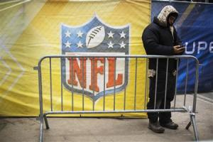 A worker looks at his phone in front of a banner on Broadway as preparations continue for Super Bowl XLVIII in New York
