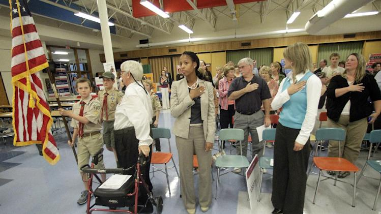 This Oct. 9, 2012, photo shows Utah Republican candidate Mia Love standing at attention as the flag enters the room during the Granite PTA meet the candidates at Skyline High School in Salt Lake City. On the road to possibly becoming the first black Republican woman elected to Congress, Love made a brief star turn at the party's convention, touching on a subject she usually downplays: race. (AP Photo/Rick Bowmer)