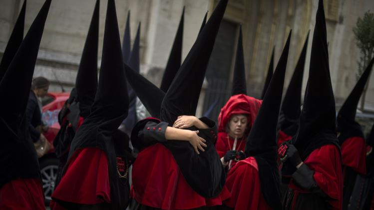 Penitents embrace before the Procesion de la Esperanza in Bilbao