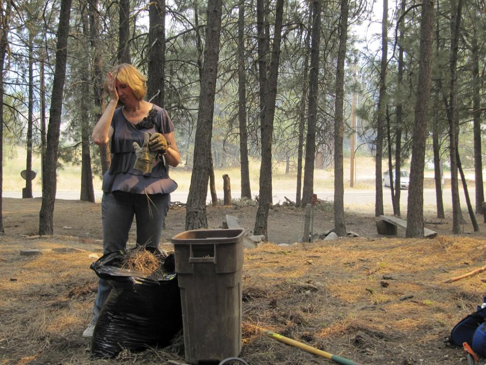 Denise Freeman rakes up pine needles to help make her log home less susceptible to a nearby wildfire in Featherville, Idaho on Wednesday, Aug. 15, 2012. Freeman was among residents warned that they will likely have to evacuate their homes because of the nearby Trinity Ridge Fire.  (AP Photo/Jessie L. Bonner)