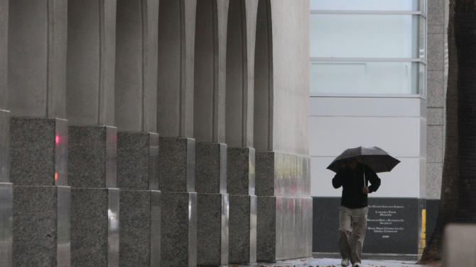 A man huddles under an umbrella as rain blankets Sacramento, Calif, Monday, Oct. 22, 2012.  The storm swept through Northern California bringing rain to the lower elevations and snow in the mountains. (AP Photo/Rich Pedroncelli)