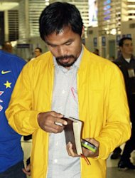 Manny Pacquiao holds his bible while preparing to board his flight to Los Angeles Saturday night<b>. RUDY SANTOS</b>