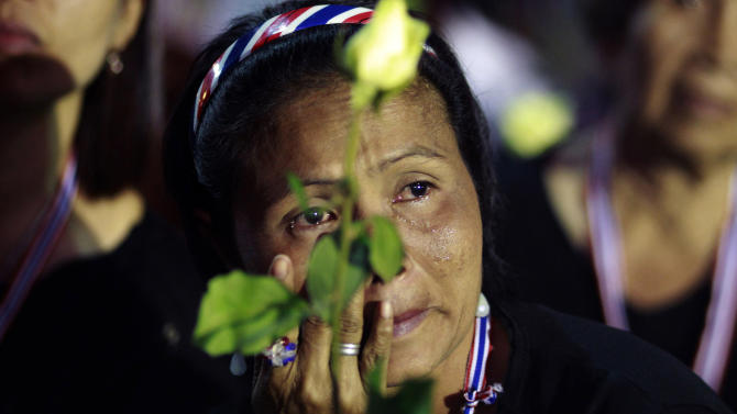 An anti-government protester cries during a condolence ceremony for the slain protester Prakong Chujan who died in Friday's grenade attack at Lumpini rally site in Bangkok, Thailand Saturday, Jan. 18, 2014. A grenade thrown into a crowd of marching anti-government demonstrators in Thailand's capital killed one man and wounded dozens of people, an ominous development that raises tensions in the country's political crisis and the specter of more bloodshed to come. (AP photo/Wason Wanichakorn)