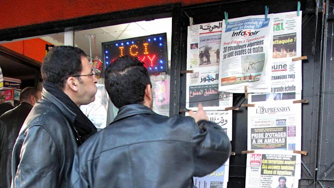 Algerian men look at national newspapers headlining the terrorist attack and kidnapping in Amenas at a news stand in Algiers, Thursday, Jan. 17, 2013. Algerian forces raided a remote Sahara gas plant on Thursday in an attempt to free dozens of foreign hostages held by militants with ties to Mali's rebel Islamists, diplomats and an Algerian security official said. Information on the Algerian assault in the remote area was wildly varying _ Islamic militants claimed that 35 hostages and 15 militants died in a strafing by Algerian helicopters, while Algeria's official news service claimed hundreds of local workers and half the foreigners were rescued. (AP Photo/Ouahab Hebbat)