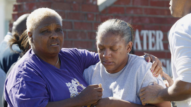 Lena Norris, left, comforts Verna Oates outside the the Greater Sweethome Missionary Baptist Church where a car crashed into the church in Forest Hill, Texas, Monday, Oct. 29, 2012. Forest Hill Police Chief Dan Dennis says the pastor of the church is dead after the driver of the car crashed into the building and began to assault him. Dennis said officers arrived Monday afternoon at the Greater Sweethome Missionary Baptist Church to find an assault in progress. Dennis says the suspected attacker also later died shortly after being detained.   (AP Photo/LM Otero)