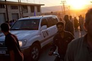 "Residents of the Syrian village of Treimsa gather around the vehicles of UN observers upon their arrival to investigate an attack on the village, where more than 150 people were killed this week, in the central province of Hama on July 13. Syria's army blasted rebel strongholds in Damascus with mortars Sunday, sparking the ""most intense"" fighting in the capital since the revolt erupted"