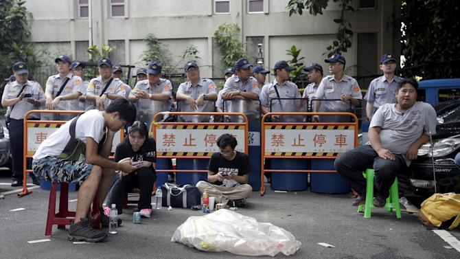 Police officers stand guard behind fences as students participate a protest at the entrance to the Ministry of Education in Taipei