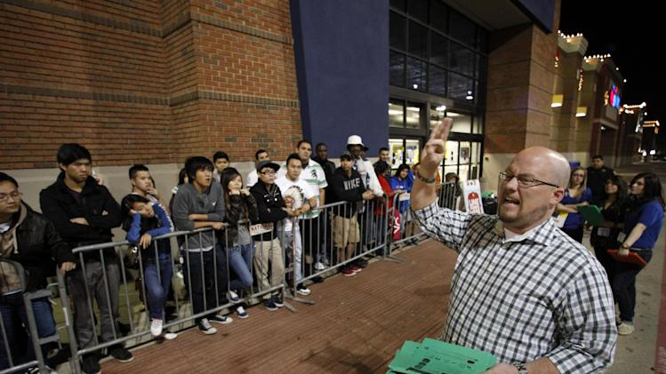 Best Buy general manager Shaun Ogdie, right,  gives instructions to shoppers before handing out  sale vouchers on popular eletronics items before the store opened at midnight Thursday Nov. 22, 2012, in Arlington, Texas. (AP Photo/Tony Gutierrz)
