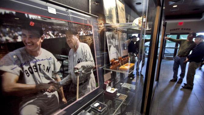 A 1943 photograph showing Boston Red Sox's Ted Williams, left, shaking hands with New York Yankees' Babe Ruth rests in a display case at Fenway Park during an auction preview of items once owned by Williams, Wednesday, April 25, 2012, in Boston. Fans are able to see hundreds of items during the preview which is to last through Friday. The auction is to be held Saturday, April 28. (AP Photo/Steven Senne)
