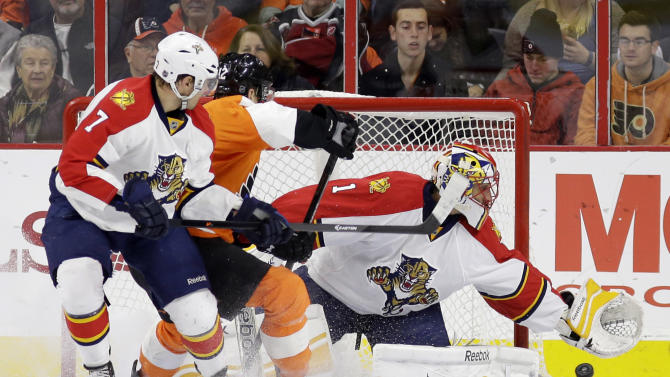 Florida Panthers' Roberto Luongo, right, reaches for a wide shot as Philadelphia Flyers' Michael Raffl, center, of Austria, and Dmitry Kulikov, of Russia, look on during the first period of an NHL hockey game, Thursday, Dec. 18, 2014, in Philadelphia. (AP Photo/Matt Slocum)