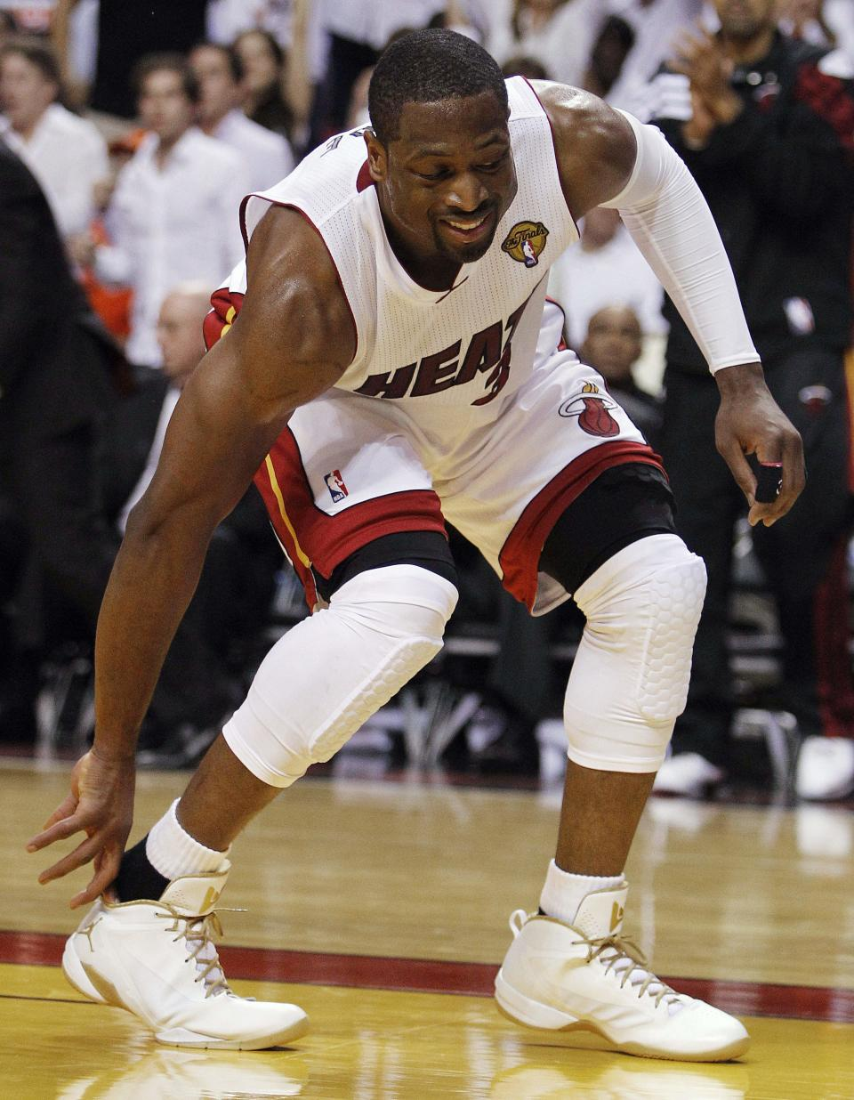 Miami Heat shooting guard Dwyane Wade (3) puts his shoe back on during the first half at Game 5 of the NBA finals basketball series against the Oklahoma City Thunder, Thursday, June 21, 2012, in Miami. (AP Photo/Lynne Sladky)