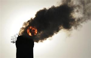 The sun is seen behind smoke billowing from a chimney of a heating plant in Taiyuan