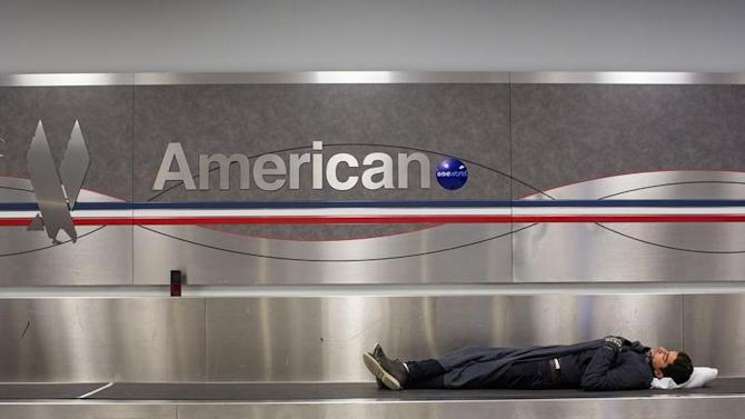 A man sleeps on a conveyer belt under an American Airlines logo at John F. Kennedy International Airport in New York