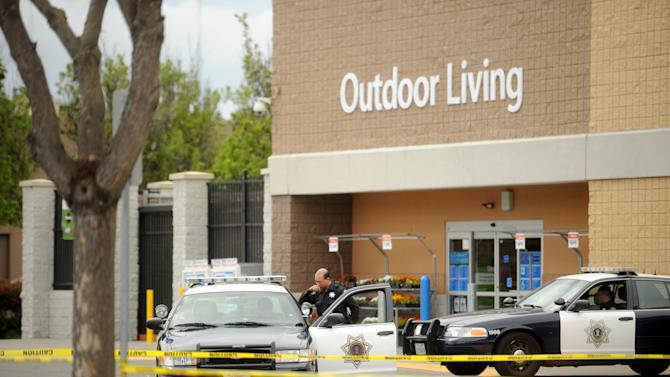 Police cars maintain a perimeter around a San Jose, Calif., Walmart after a motorist drove through a store entrance and began assaulting shoppers on Sunday, March 31, 2013. Four people sustained injuries during the attack according to a police spokesman. (AP Photo/Noah Berger)