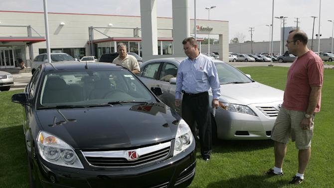 FILE - In this June 8, 2007 file photo, Vince Olsen, center, manager of the Saturn of Troy dealership in Troy, Mich., shows off a 2007 Saturn Aura. Federal safety regulators are investigating problems with the automatic shift levers on several General Motors Co. cars that have caused at least seven crashes. The National Highway Traffic Safety Administration said on its website Monday, Nov. 14, 2011, that the probe began with complaints about the Saturn Aura midsize car from the 2007 and 2008 model years, affecting nearly 89,000 vehicles. (AP Photo/Carlos Osorio, File)