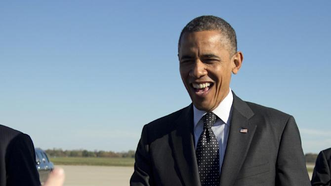 President Barack Obama greets people on the tarmac as he arrives at Rickenbacker Inland Port on Air Force One, Tuesday, Oct. 9, 2012, in Columbus, Ohio. (AP Photo/Carolyn Kaster)