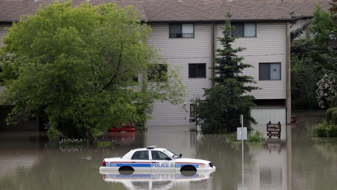 A police car sits stuck in a parking lot of an apartment building after heavy rains have caused flooding, closed roads, and forced evacuation in Calgary, Alberta, Canada Friday, June 21, 2013. (AP Photo/The Canadian Press, Jeff McIntosh)