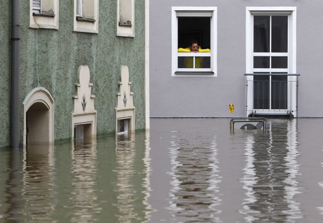 A man looks at flood water from the upstairs window of a house in the centre of Passau