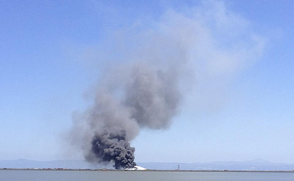 In this photo provided by Scott Sobczak, smoke rises from of Asiana Flight 214 after it crashed at San Francisco International Airport in San Francisco, Saturday, July 6, 2013. (AP Photo/Scott Sobczak) MANDATORY CREDIT