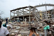 People search the wreckage of Saint Louis Church in the Mpila district of Brazzaville. The death toll from powerful explosions at a Congo munitions dump approached 200 on Tuesday, as international aid began to arrive to help treat over 1,300 wounded and assist 5,000 homeless