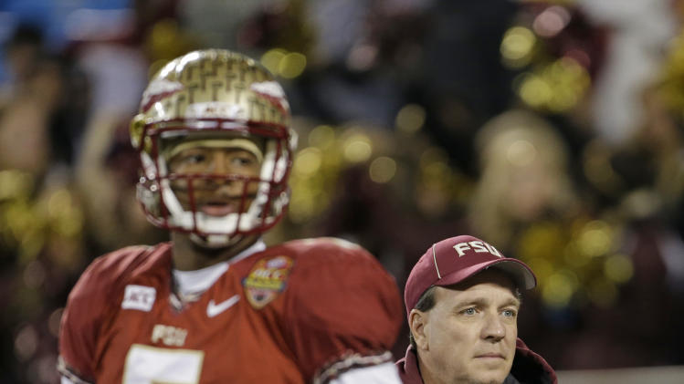 Florida State head coach Jimbo Fisher, right, looks on as Jameis Winston, left, warms up before the Atlantic Coast Conference Championship NCAA football game between Florida State and Duke in Charlotte, N.C., Saturday, Dec. 7, 2013. (AP Photo/Bob Leverone)