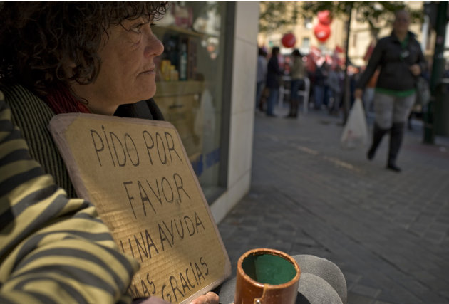 Alice, a homeless woman, left,  begs for alms, as people protest against the government's tough new labor reforms and cutbacks in Pamplona, northern Spain, Tuesday, May 1, 2012. Banging drums and wavi