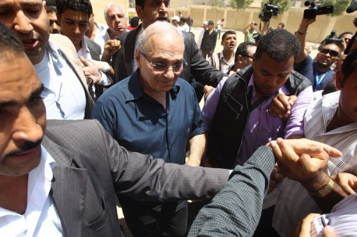 <p>Egypt's presidential candidate Ahmed Shafiq (centre) leaves a polling station in Cairo after casting his vote on June 16. Shafiq on Monday angrily dismissed claims of victory by his rival Mohammed Mursi, accusing the Muslim Brotherhood candidate of using false figures.</p>
