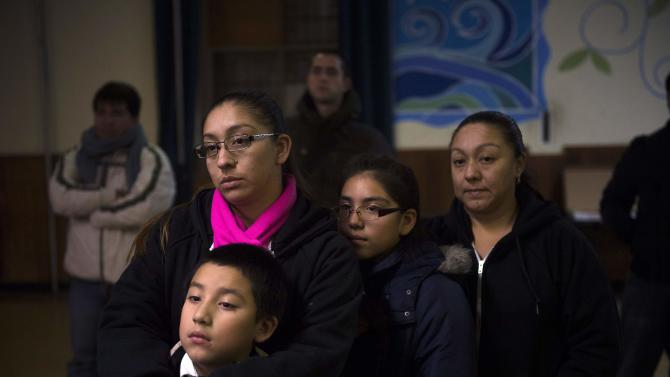 Undocumented immigrant Mota, holds her son, a U.S. citizen, as they watch President Obama announce executive action on immigration, at the West Kensington Ministry church, in Philadelphia