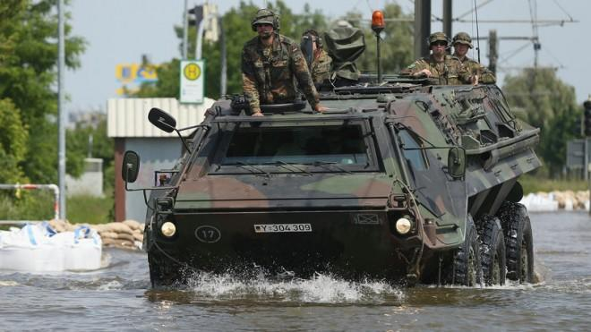 German soldiers ride an amphibious transporter through floodwaters from the swollen Elbe river on June 9 in Magdeburg.